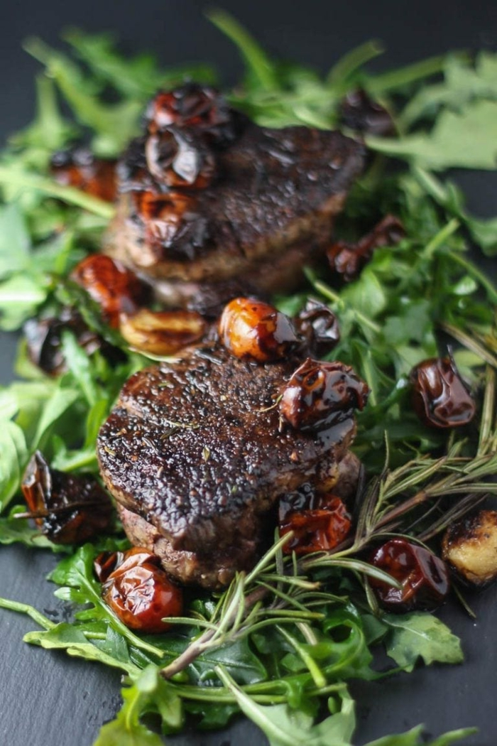 fillet mignon recipe, balsamic tomatoes, dinner ideas for two, green salad underneath, placed on black surface