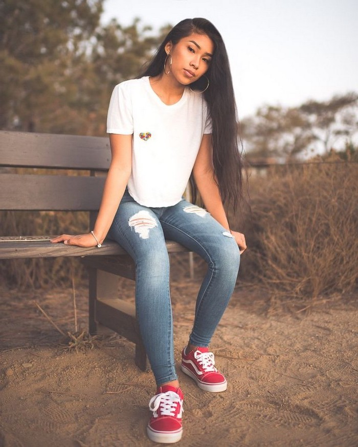 first day of school outfits, girl with long black hair, sitting on a bench, wearing jeans and white t shirt, red vans shoes