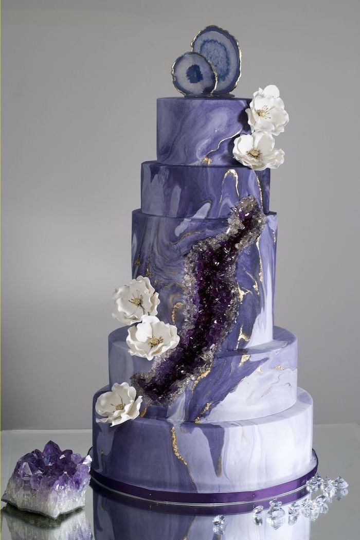 five tier cake, covered with purple and white marble fondant, geode cupcakes, decorated with purple rock candy and flowers