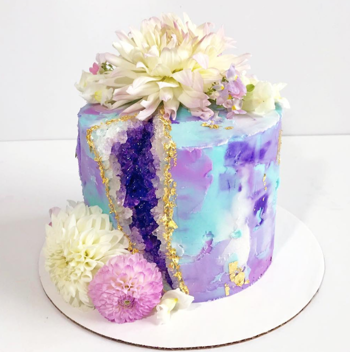 one tier cake with colorful buttercream, geode cupcakes, decorated with white and purple rock candy and flowers