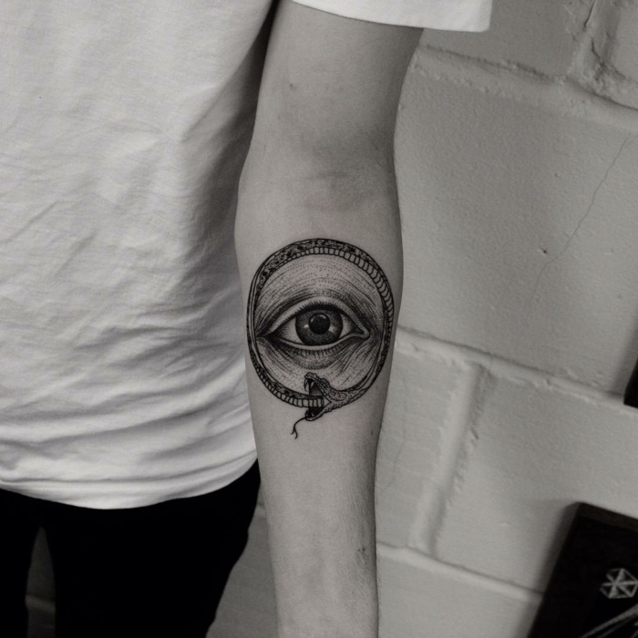 forearm tattoo, eye surrounded by a snake, ouroboros tattoo, black and white photo, white brick wall background