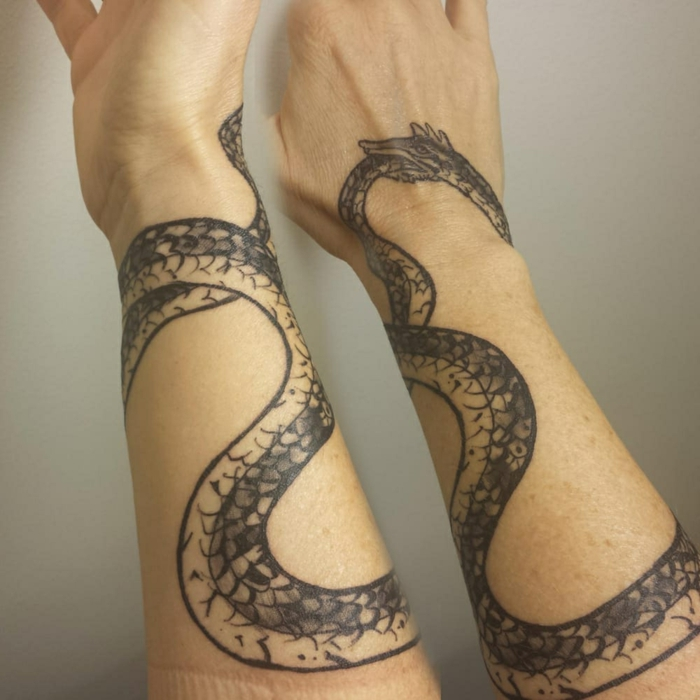 forearm tattoo of a serpent wrapped around the whole forearm, snake eating its tail, white background