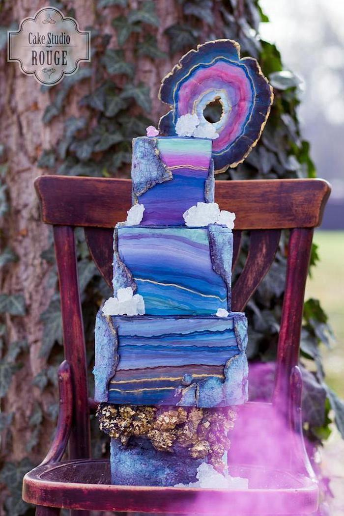 four tier cake, covered with colorful galaxy fondant, geode cupcakes, decorated with galaxy painted rock candy