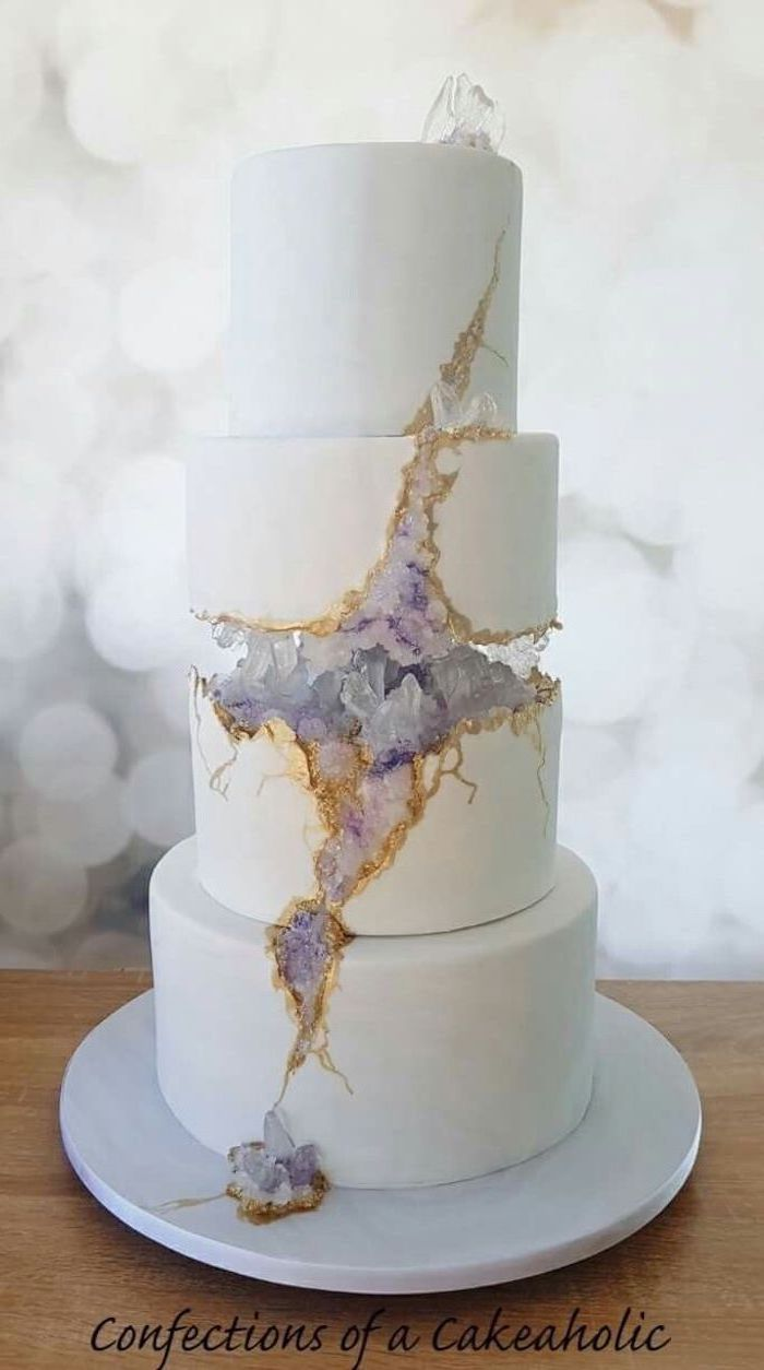 four tier cake, covered with white fondant, decorated with white and purple rock candy, how to make a geode cake