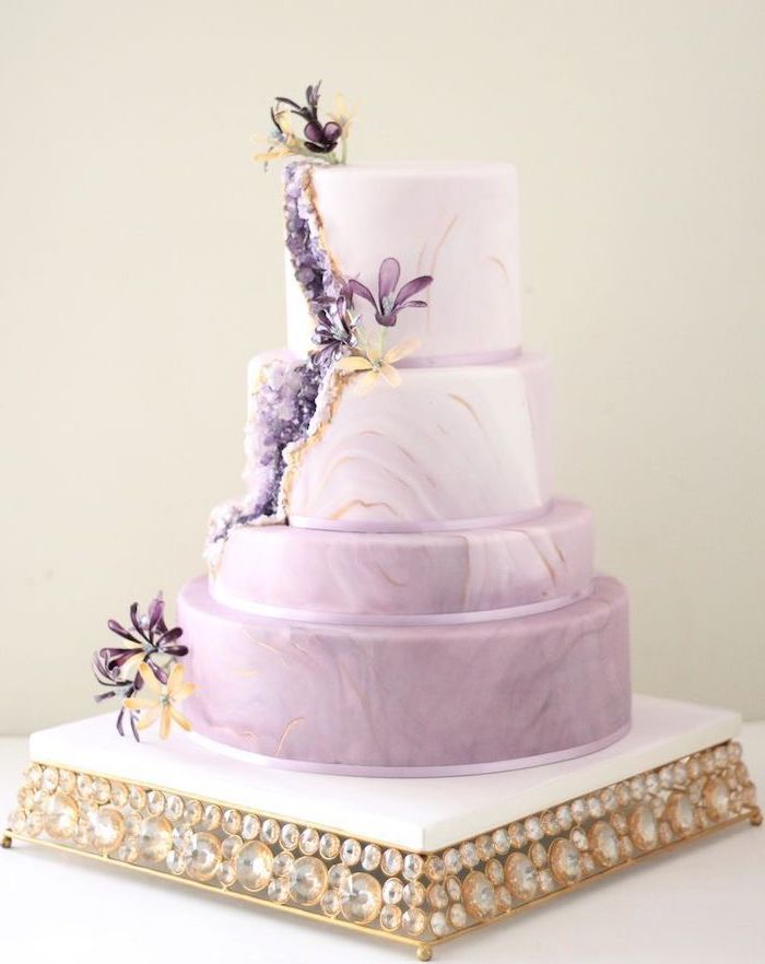 four tier cake, covered with purple and white marble fondant, how to make a geode cake, decorated with purple rock candy and flowers