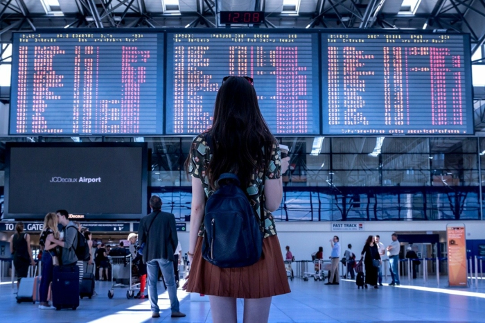 girl wearing a skirt and backpack, standing in the airport, cheapest flights, looking at planes timetables