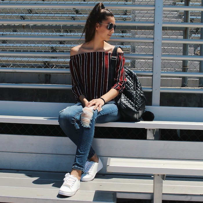 brunette woman sitting on a bench, first day of school outfits, wearing jeans and red and black shirt, white sneakers