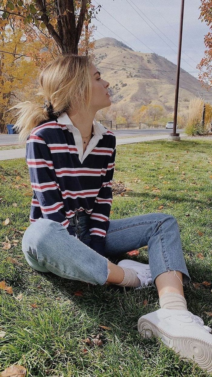 fall outfits for girls, girl sitting on the grass, wearing washed jeans, navy blue and red striped blouse, white sneakers
