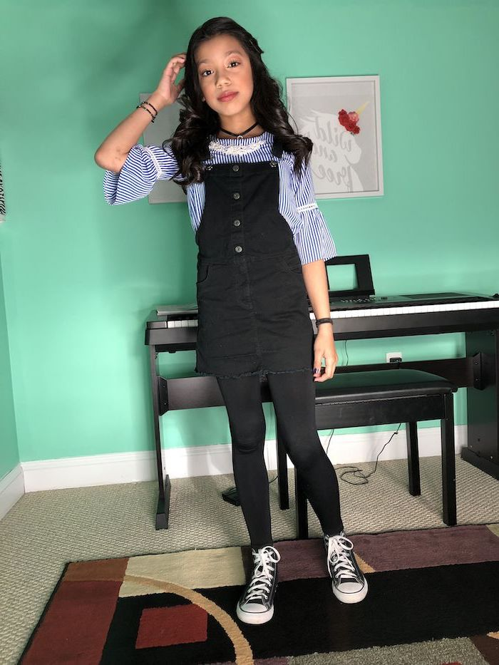 girl wearing black denim overalls, blue and white striped shirt, fall outfits for girls, black low top converse shoes