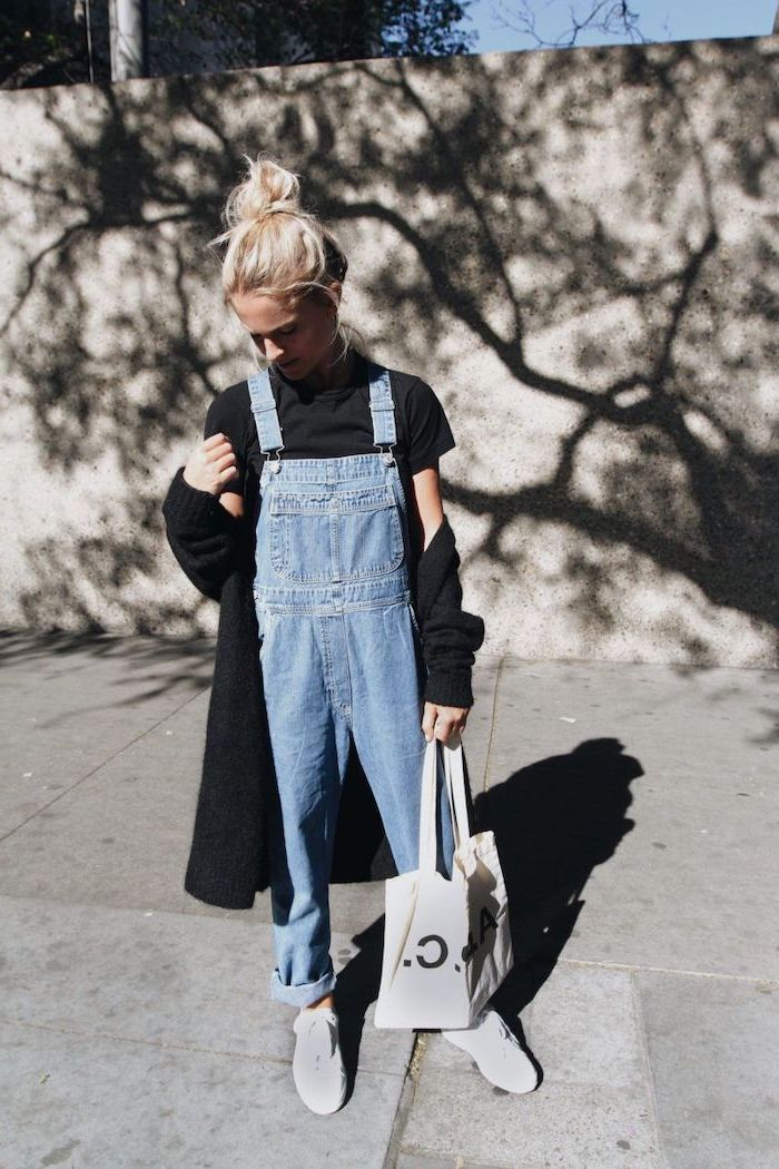 blonde girl wearing denim overalls, black shirt and cardigan, fall outfits for girls, white sneakers