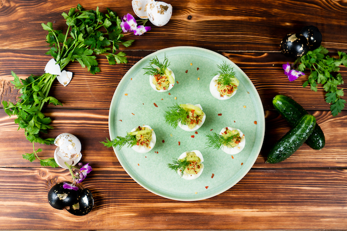 green plate placed on wooden surface easter eggs stuffed with egg yolk mixture decorated with dill cucumber slices