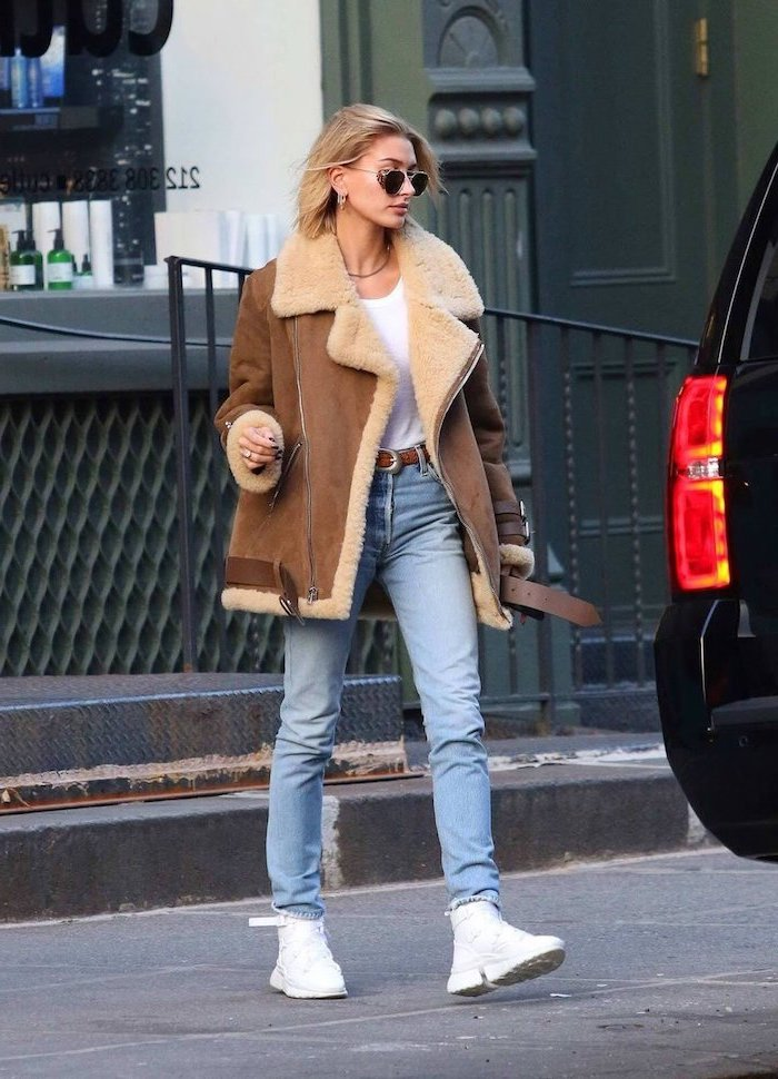 hailey bieber walking on the road, wearing jeans and white t shirt, brown jacket and white sneakers, first day of school outfits