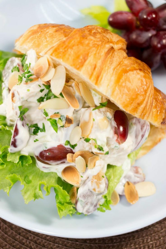 halved croissant, filled with lettuce and grapes, almonds and sauce inside, easter menu ideas 2019, placed on white plate