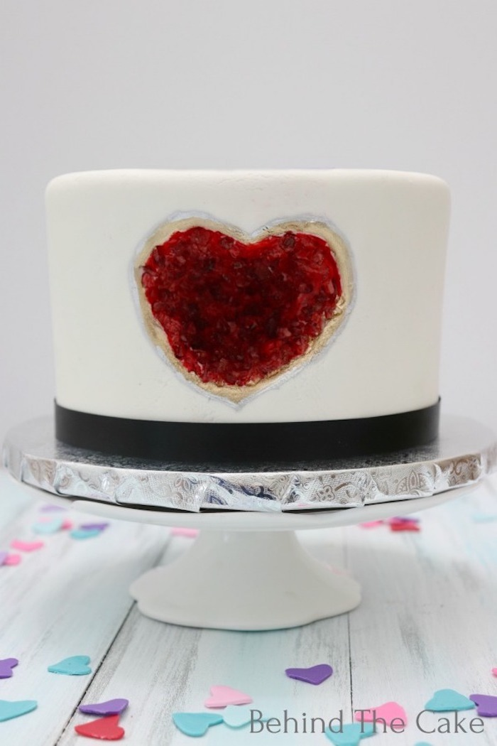 one tier cake, covered with white fondant, decorated with heart shaped red rock candy, amethyst cake, placed on white cake stand