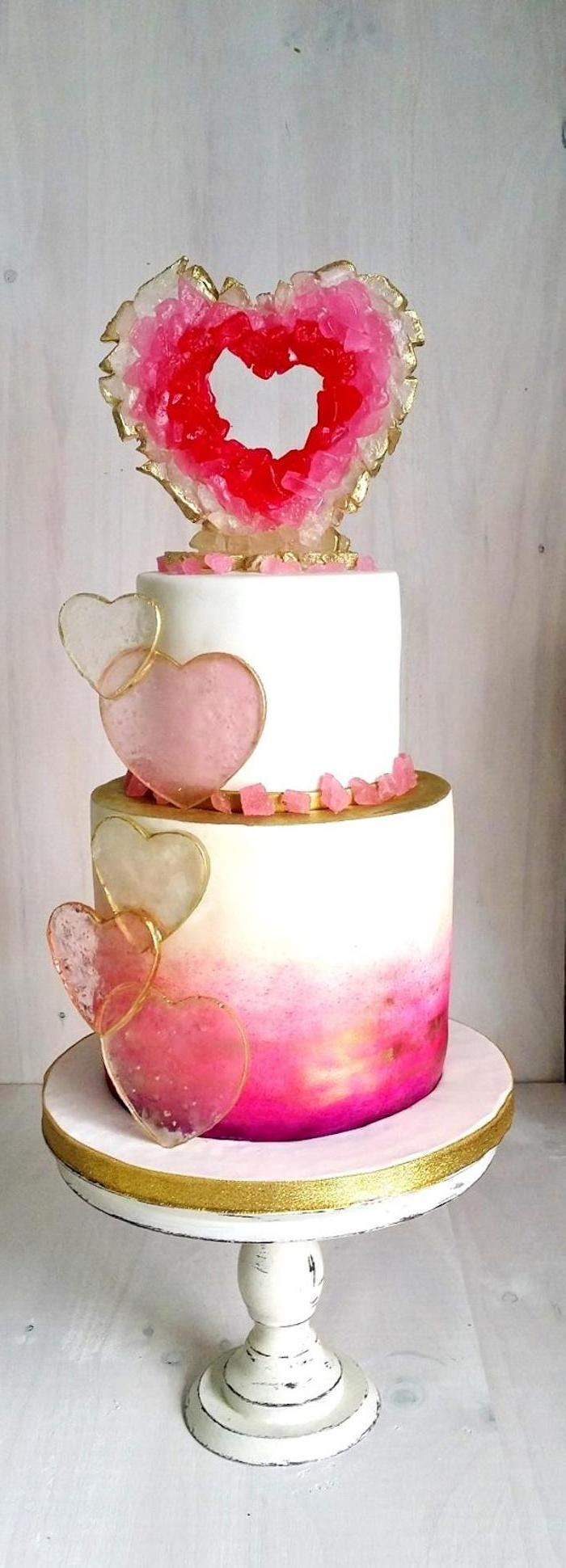 geode cake recipe, two tier cake, covered with pink and white fondant, decorated with pink heart shaped rock candy