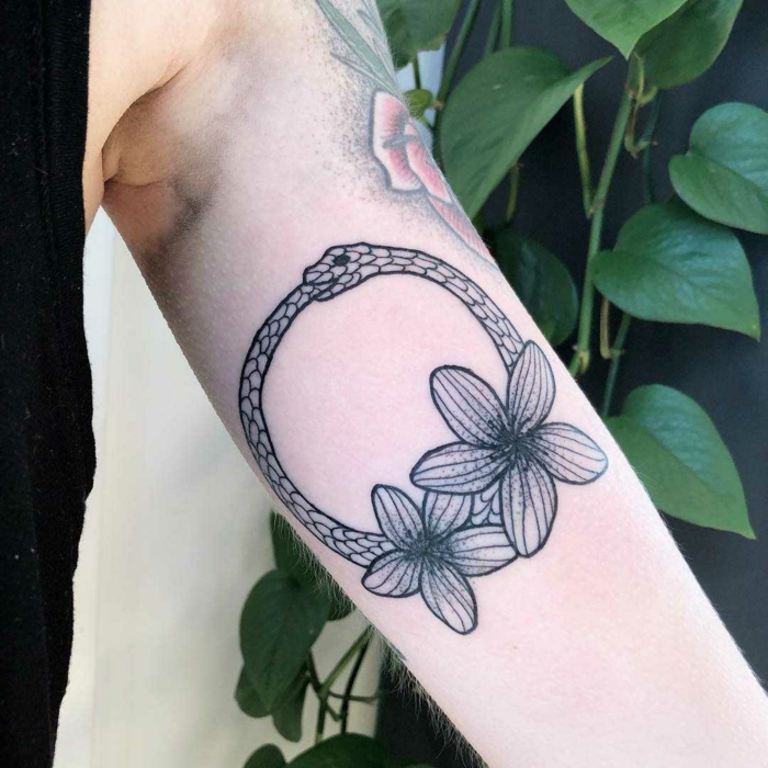 inside of the arm tattoo, ouroboros symbol, snake with two flowers underneath, mand wearing black top