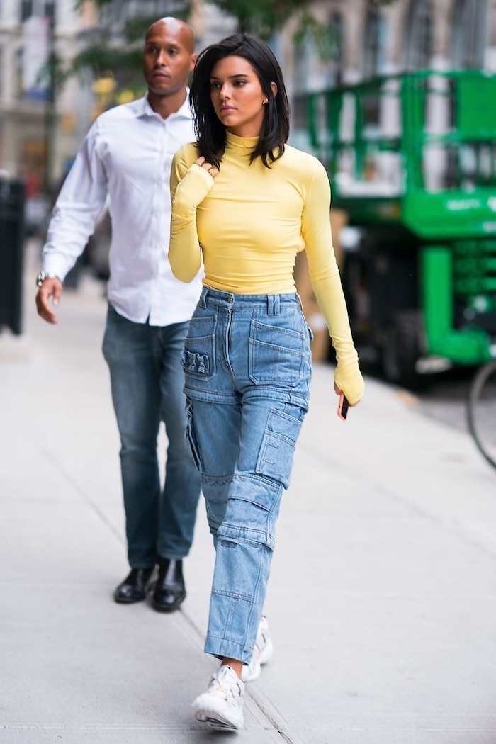 kendall jenner walking on a sidewalk, cute outfits with leggings, wearing jeans with lots of pockets, yellow polo blouse