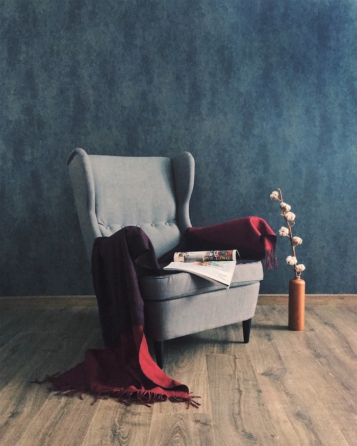 wooden floor, grey armchair with throw blanket on it, laminate flooring, blue wall and small vase with flower