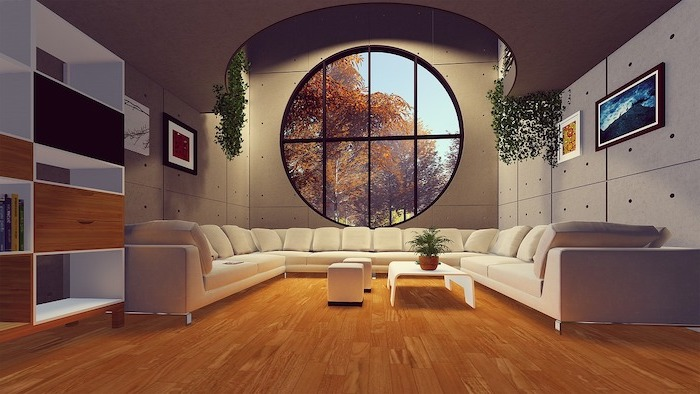 large living room with large white sofa, laminate flooring, wooden floor and large round window, white coffee table and ottomans