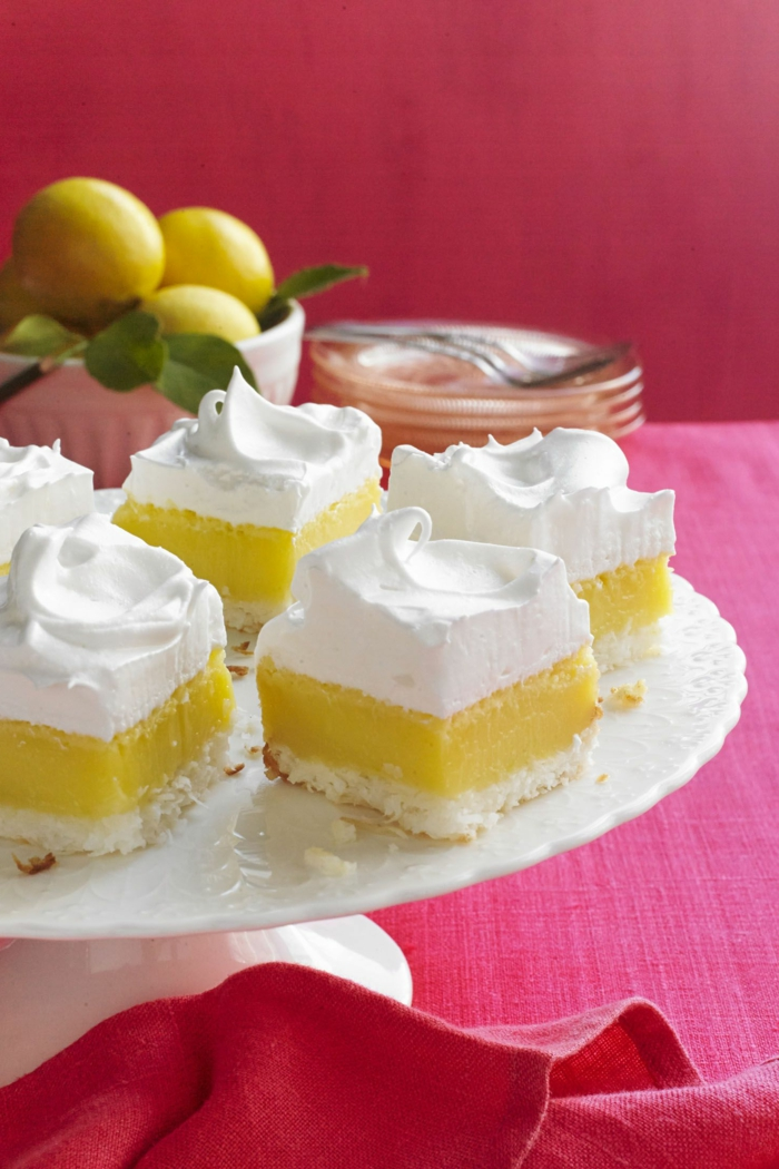 lemon pie cut into pieces, arranged on white cake stand, traditional easter food, red table cloth
