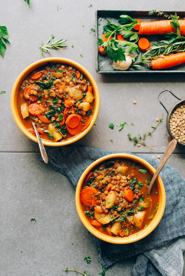 lentil sop with carrots and potatoes, poured in two ceramic bowls, quick and easy dinner recipes, placed on grey table