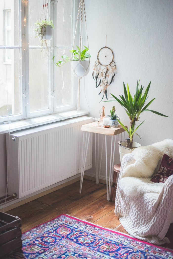 living room with wooden floor and white walls, plants hanging from the ceiling, macrame plant hanger diy, small armchair on the side