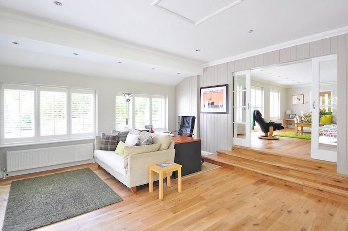 living room with white sofa with throw pillows, laminate flooring, grey carpet on wooden floor, wooden desk with black chair