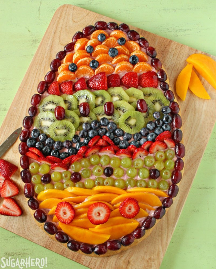 traditional easter food, dfferent fruits arranged in the shape of an egg, wooden cuttin board