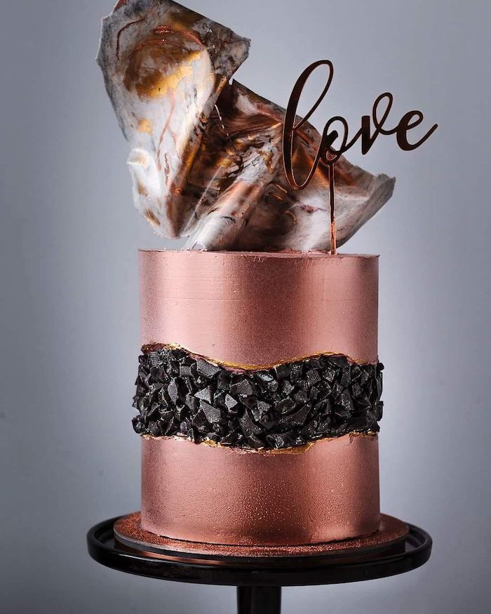 one tier cake, covered with rose gold fondant, geode cake recipe, decorated with black rock candy in the middle
