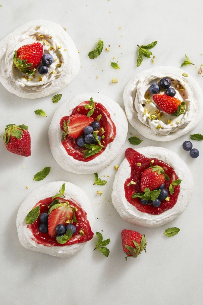 mini pavlovas, easter dinner ideas 2019, strawberries and blueberries on top, arranged on white surface