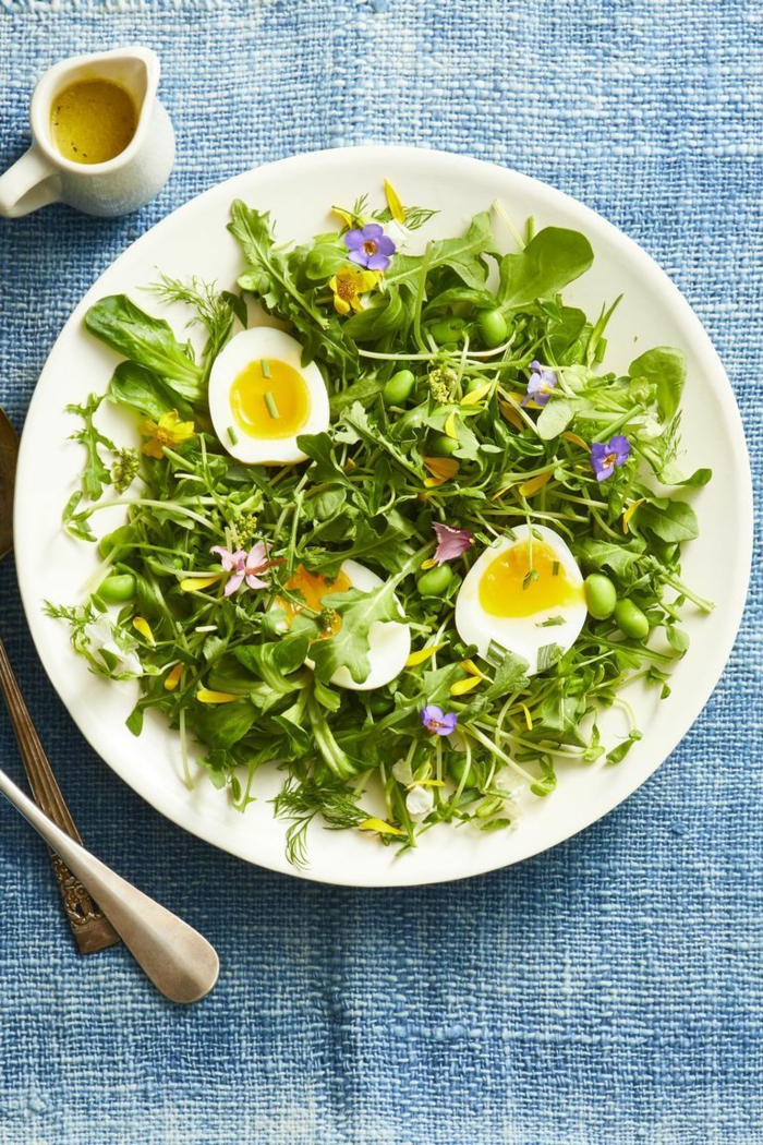 mixed green herb toss salad, halved boiled egg on top, placed in white plate, easter dinner ideas 2019, blue table cloth