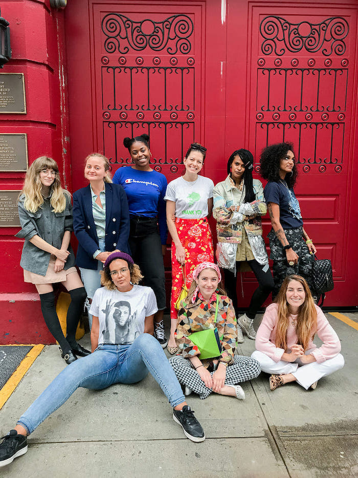 a large group of girls posing for a photo, large red door behind them, dressed in different outfits, middle school outfits