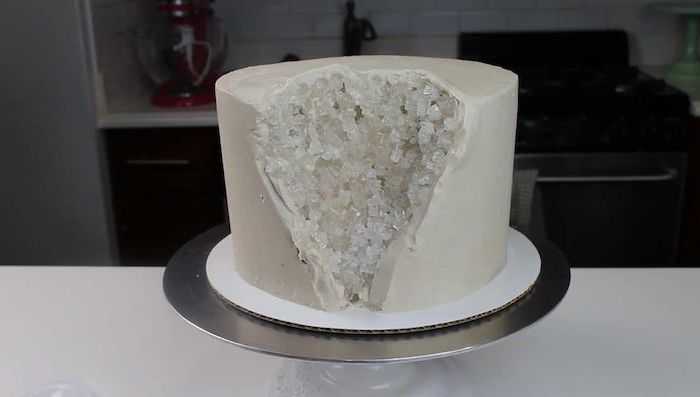 crystal cake, one tier cake covered with white fondant, white rock candy placed on the side, placed on silver cake stand