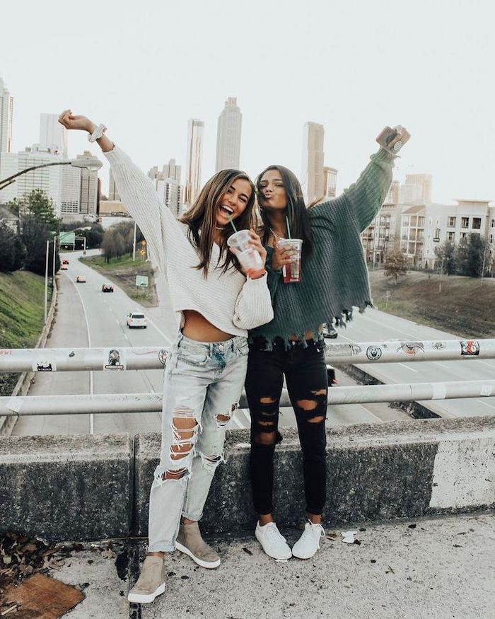 two girls standing on a bridge over a highway, middle school outfits, wearing ripped jeans and knitted sweaters