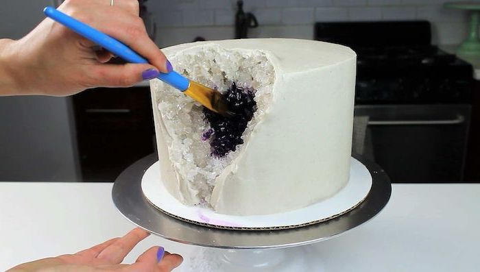 one tier cake, covered with white fondant, crystal cake, white rock candy painted in purple, placed on silver cake stand