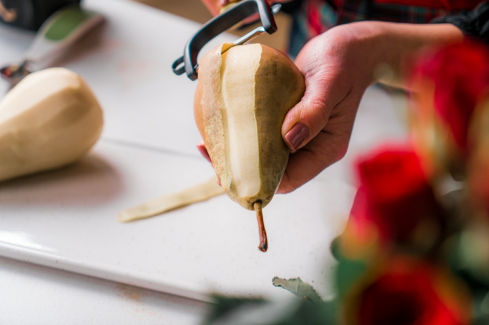 poached pears, pear being peeled with black julienne peeler, white cutting board