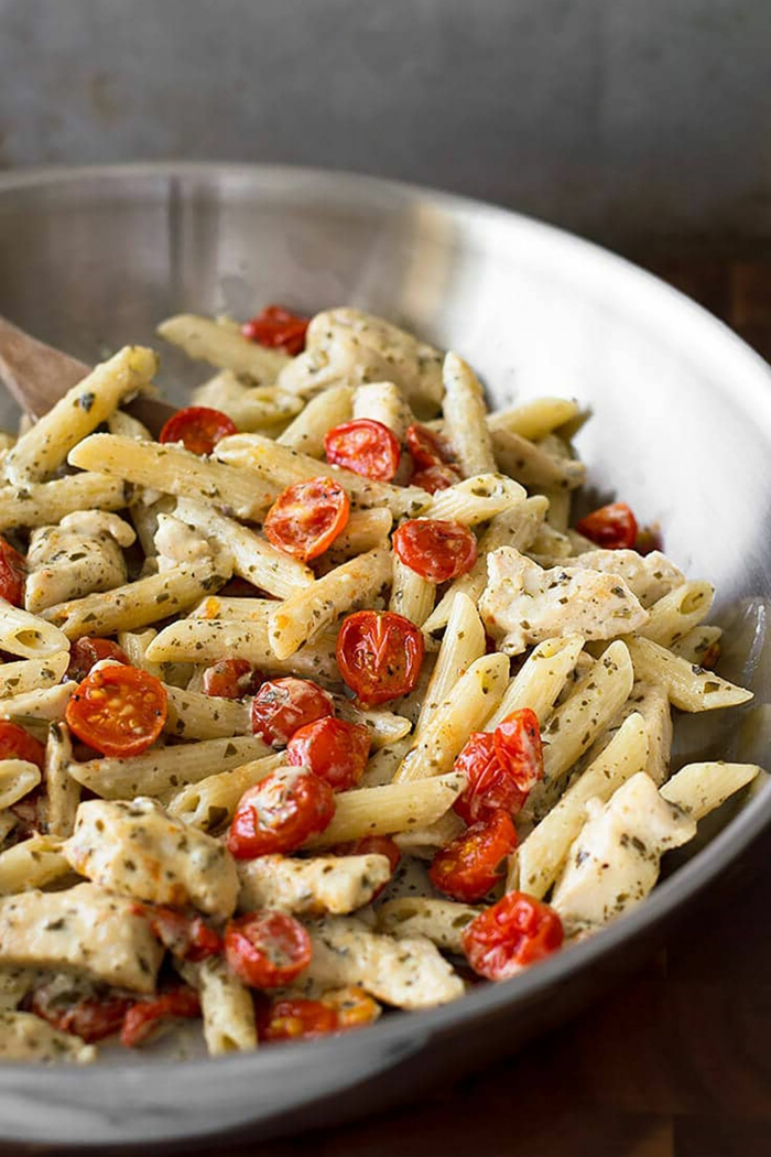 pesto chicken pasta, garnished with halved cherry tomatoes, easy dinners for two, cooked in metal sauce pan