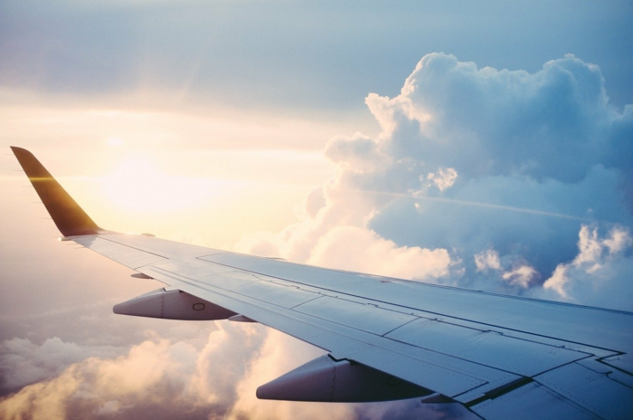 wing of a plane, flying above the clouds, photographed from inside the plane, cheapest flights, sun shining