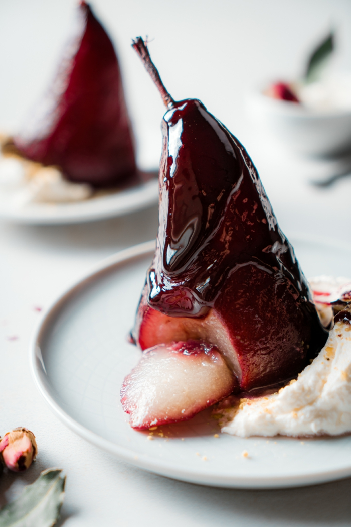 wine and sugar reduction drizzled, poached pears, served with cream on white plate