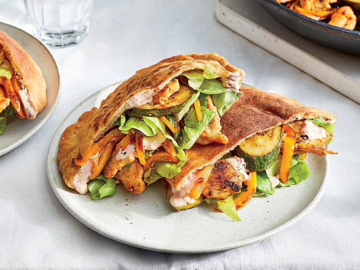 pita bread with chicken and vegetables inside, easy dinners for two, placed on white plate on white surface