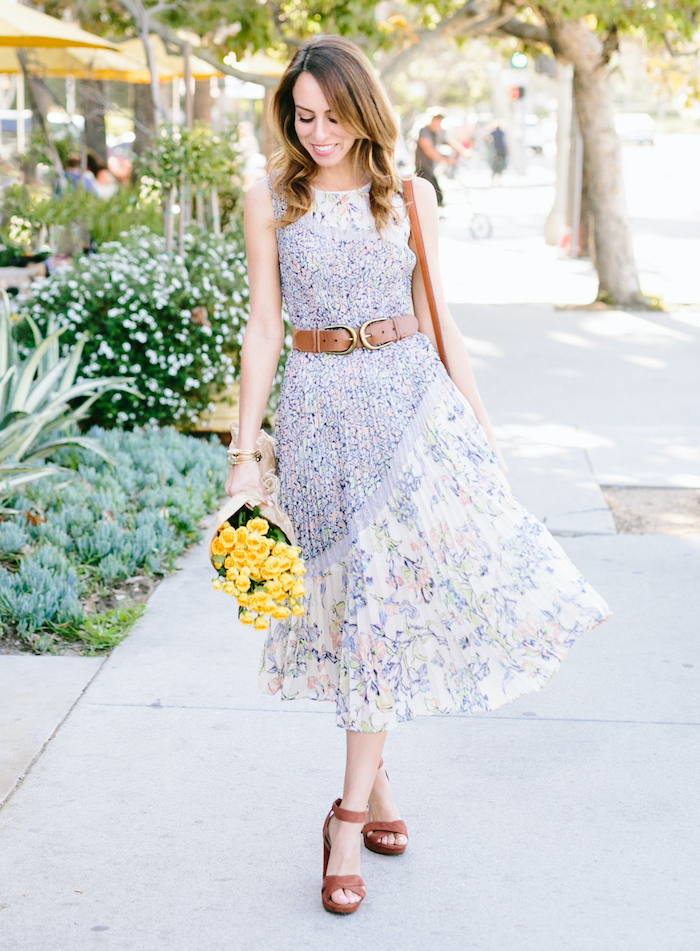 woman walking down the sidewalk, wearing a white dress with floral print, pretty dresses for women, holding a bouquet of yellow flowers