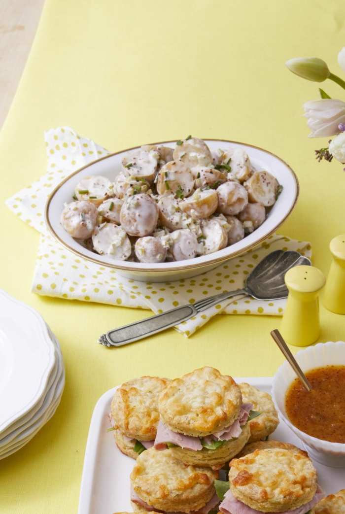 potato salad with creamy sauce in white bowl, easter dinner ideas no ham, small sandwiches with ham on the side