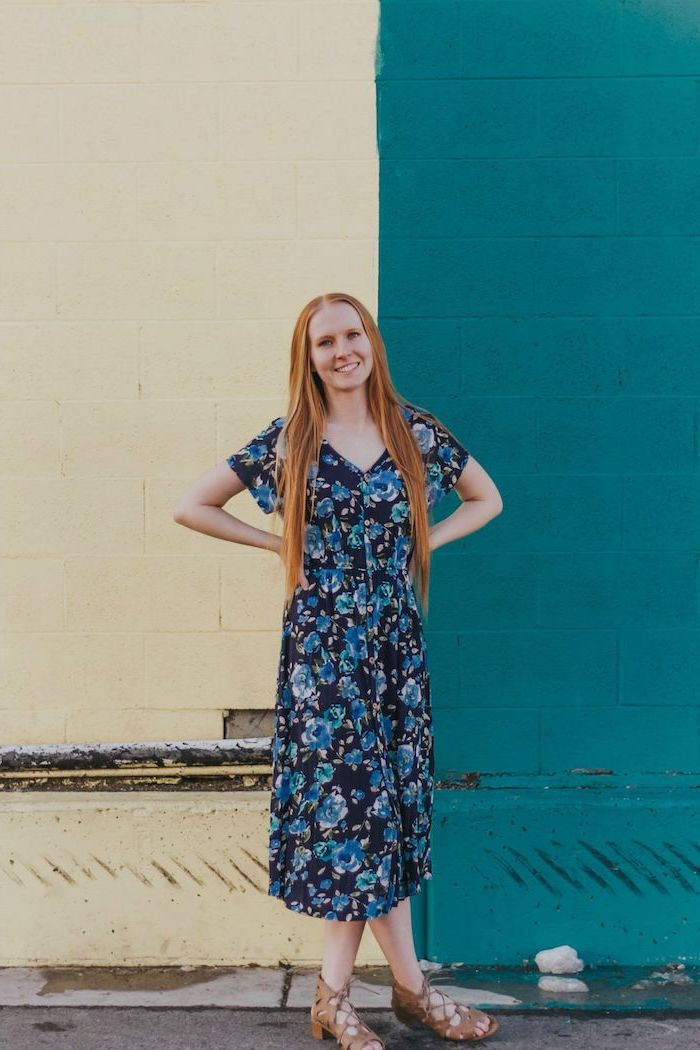 woman with long red hair, wearing a navy blue dress with floral print, brown flat sandals, pretty dresses for women