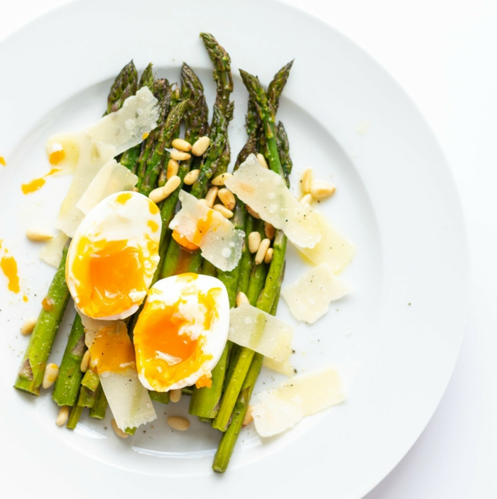 roasted asparagus with seeds, halved boiled egg and parmesan on top, placed on white plate, easter buffet 2019