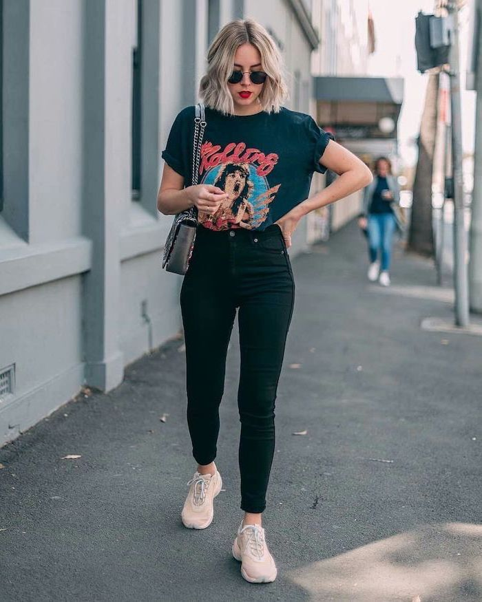 blonde woman walking on a sidewalk, wearing black jeans, black rolling stones t shirt, cute first day of school outfits, white sneakers