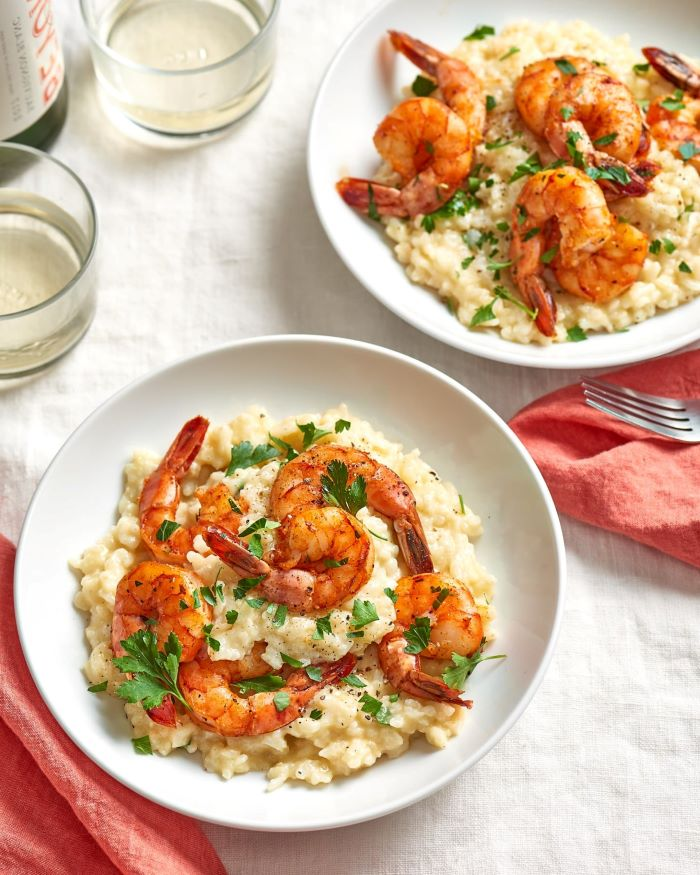 shrimp risotto, easy dinner ideas for two, garnished with parslye, placed in white plates