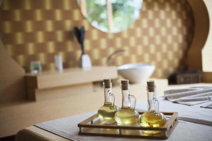 three glass bottles, filled with different oils, placed on a tray, spa holidays, placed on white surface
