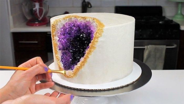 one tier cake, covered with white fondant, decorated with rock candy, painted in purple and gold, crystal cake