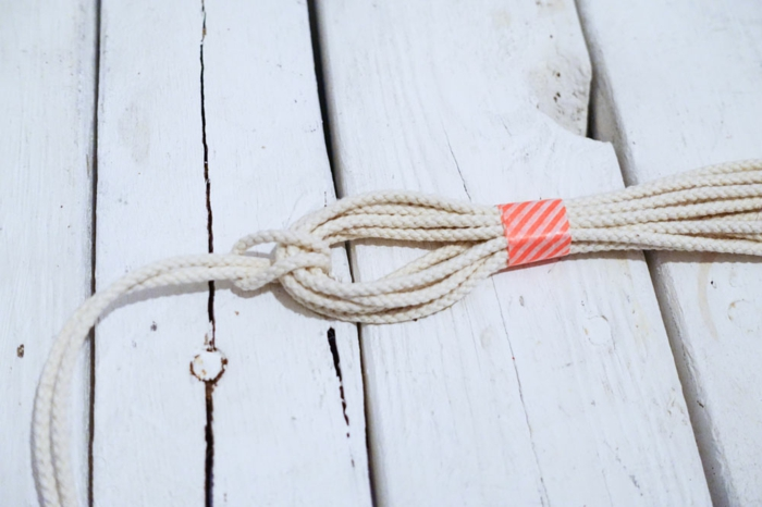 strands of macrame held together with tape, macrame plant hanger, step by step diy tutorial
