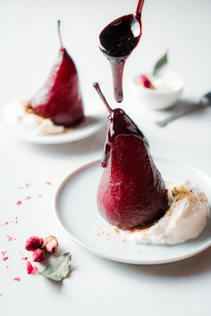 wine and sugar reduction drizzled, poached pears in red wine, served with cream on white plate
